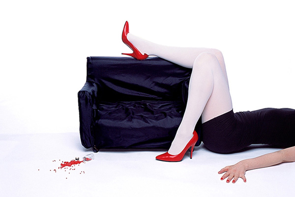 Woman wearing red high-heeled shoes lying on the floor with her leg on a miniature sofa and a bottle of red pills spilled on the floor