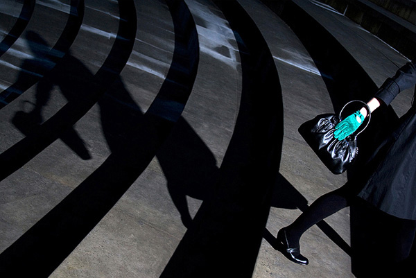 Woman in high heels holding a handbag with a green gloved hand walking up steps and casting a distorted shadow behind her
