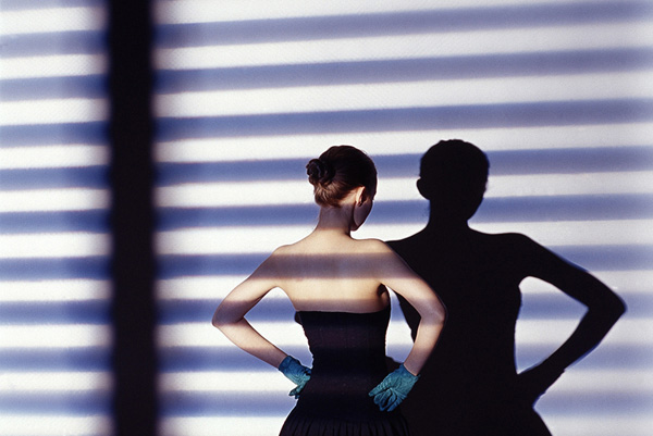 Shadow from a Venetian blind cast onto a woman with her back to the camera
