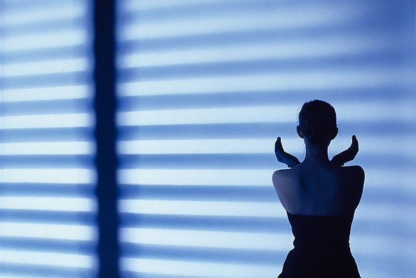 Blue light of a shadow from a Venetian blind cast onto a woman with her back to the camera