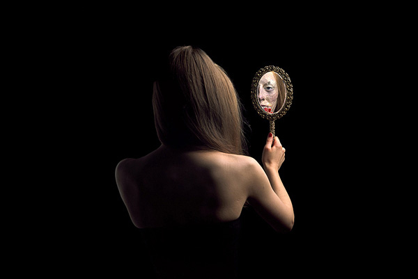 Young woman looking into a face mirror with her back to the camera, her reflection is the mask of an old woman